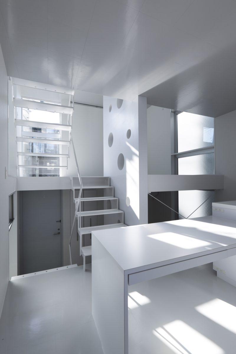 M2Fキッチン・ダイニングより2F寝室、1F玄関を見る。建築の水平要素である床と天井は、光沢のある同一の素材を採用し、 「フロアの建築」を表象している