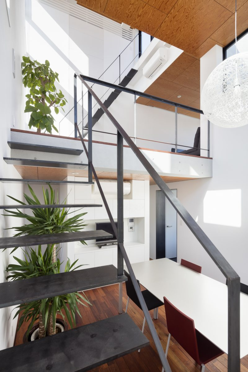 2F ダイニング。床・天井の水平面には木質系の仕上げ。RC打ち放しの梁、黒皮鉄板を用いたキャンティレバーの階段など豊かな素材感を持つインテリア。