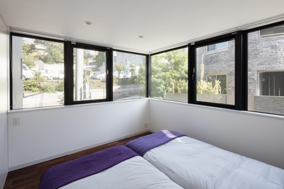 1F 寝室。道路から少し高いレベルに設けられたコーナー窓。
