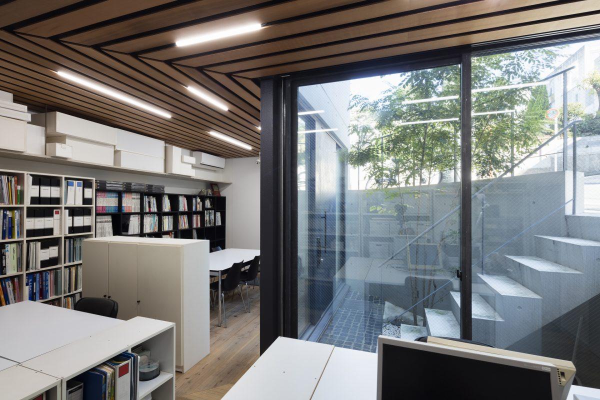B1F オフィス。L型の平面形をもつ。GLから半層低いレベルにある。右手はドライエリア。天井はベイスギ厚9mm目透かし貼り。